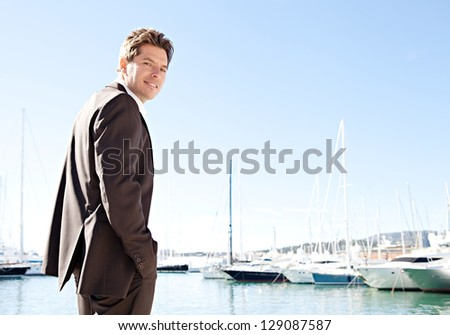 Side view of a smart businessman standing by moored sailing boats in a coastal city against a blue sky, smiling. - stock photo