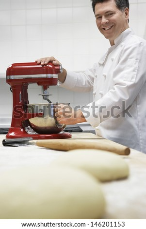 Side view of a smiling male chef using dough mixer in kitchen with focus on dough in foreground - stock photo