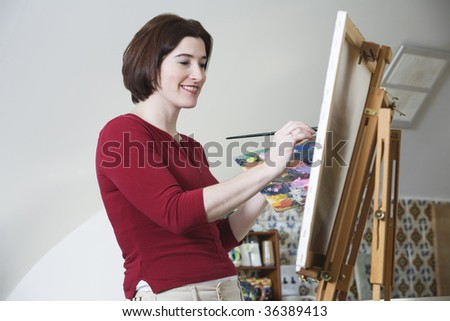 Side view of a smiling young woman painting. - stock photo