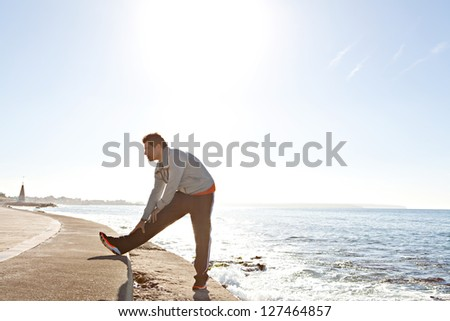 Side view of a sports man stretching his legs after exercising by the sea, next to the water, against a blue sky background. - stock photo