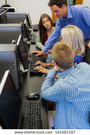 Side view of a teacher explaining to young college students in the computer room - stock photo