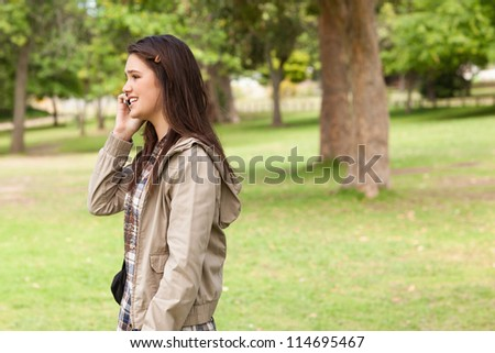 Side view of a teenager phoning in a park - stock photo