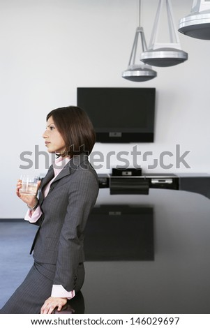Side view of a thoughtful businesswoman leaning against table in conference room - stock photo