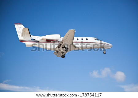 Side view of a twin engined plane flying midair coming in to land or taking off with its wheels and undercarriage still extended against a clear blue sky - stock photo