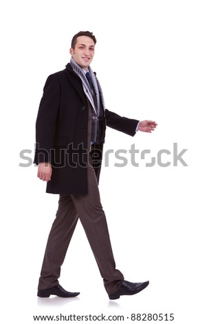 side view of a walking business man, looking to the camera, on white background - stock photo