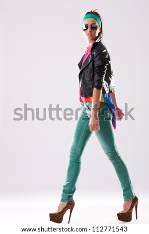 side view of a walking young woman wearing casual clothes, jacket and high heels and looking at the camera - stock photo