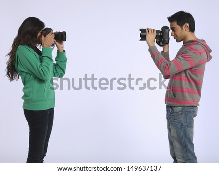 Side view of a woman and young man photographing each other in studio - stock photo