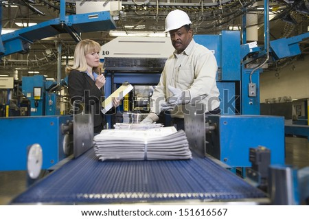 Side view of a woman by man working on newspaper production line in newspaper factory - stock photo