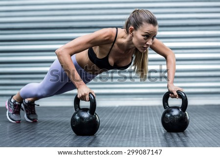 Side view of a woman doing pushups with kettlebells - stock photo