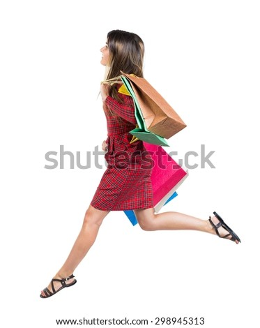 side view of a woman jumping with shopping bags. beautiful brunette girl in motion.    Isolated over white background. Long-haired girl in a red plaid dress jumping with colored paper bag. - stock photo