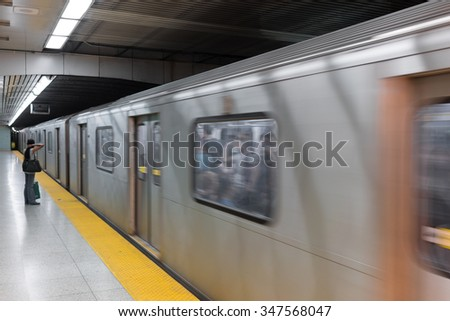 Side view of a woman on subway platform looking at train passing through, Toronto, Ontario, Canada - stock photo