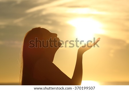 Side view of a woman silhouette kissing the sun on the beach at sunset - stock photo