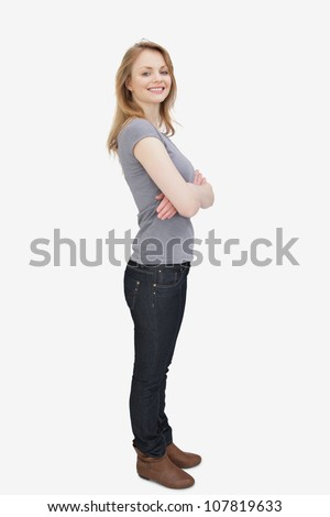 Side view of a woman smiling with arms crossed against a white background - stock photo
