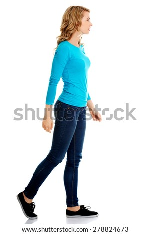 Side view of a woman walking slowly. - stock photo