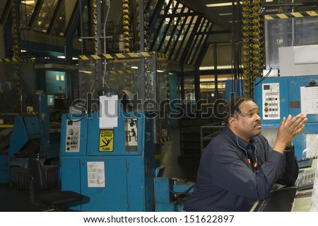 Side view of a worker in the newspaper factory - stock photo
