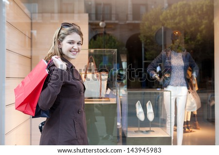 Side view of a young attractive consumer woman visiting the fashion stores in the city, walking past a shopping display window and carrying paper bags, smiling. - stock photo
