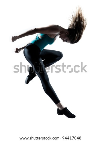 Side view of a young beautiful girl doing gymnastic jump in studio on white background - stock photo