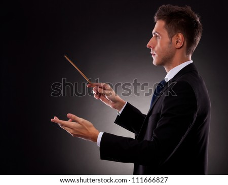 Side view of a young business man directing with a conductor's baton - stock photo