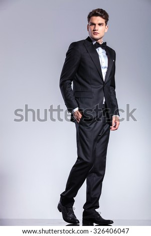 Side view of a young business man walking with his hand in pocket on studio background. - stock photo