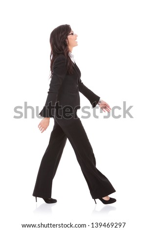 side view of a young business woman walking forward and laughing. on white background - stock photo