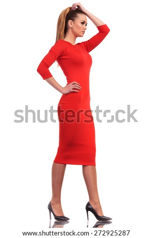 Side view of a young business woman walking on isolated studio background while holding her hand on her head. - stock photo
