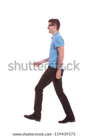 side view of a young casual man walking and looking forward. on white background - stock photo