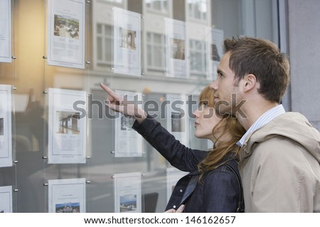 Side view of a young couple looking at window display at real estate office - stock photo