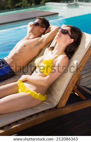 Side view of a young couple resting on sun loungers by swimming pool - stock photo