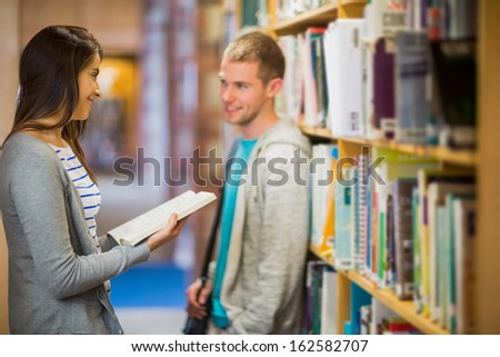Side view of a young couple standing against bookshelf in the library - stock photo