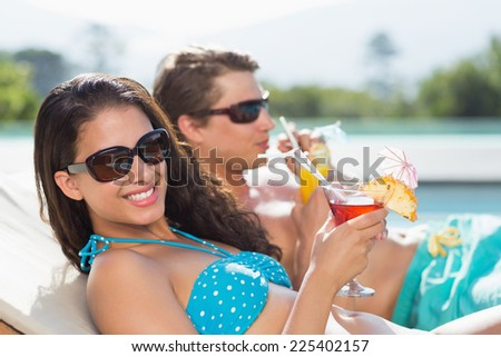Side view of a young couple with drinks by swimming pool - stock photo