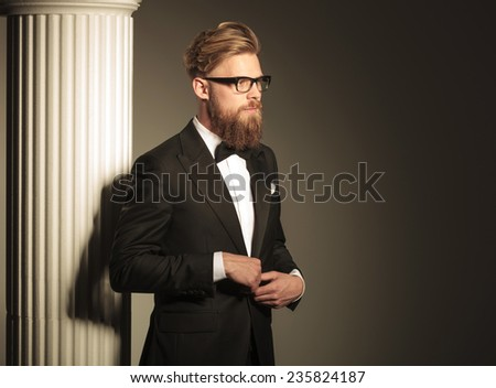 Side view of a young elegant business man looking away from the camera while closing his jacket. - stock photo