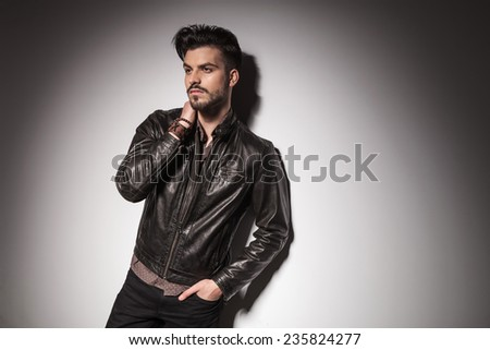 Side view of a young fashion man leaning on a wall, looking away from the camera while holding one hand in his pocket and the other on to his neck. - stock photo
