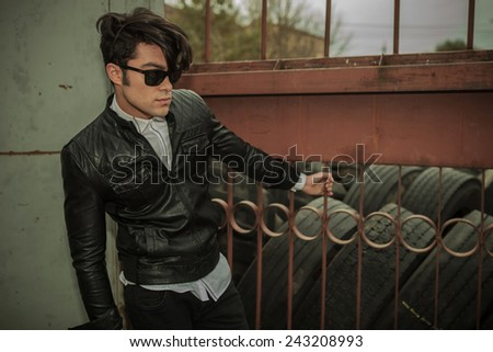 Side view of a young fashion man looking away while holding his hand on a brown fence. - stock photo