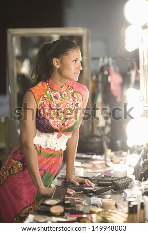 Side view of a young fashion model standing with cosmetics at dressing room - stock photo