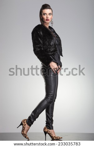 Side view of a young fashion woman stepping forward while looking up. On grey studio background. - stock photo