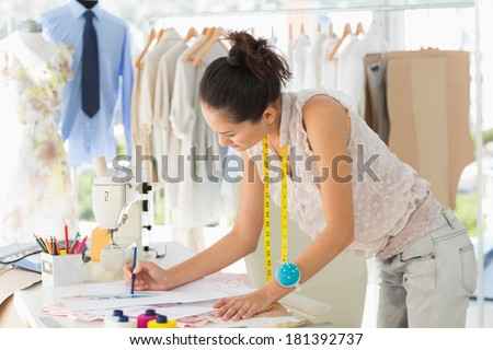 Side view of a young female fashion designer working on her designs in the studio - stock photo