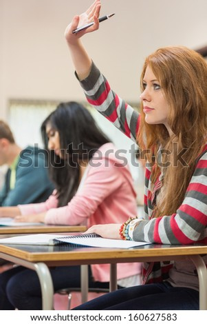 Side view of a young female student raising hand by others in the classroom - stock photo