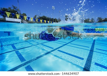 Side view of a young female swimmer in pool - stock photo