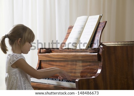 Side view of a young girl playing the piano - stock photo