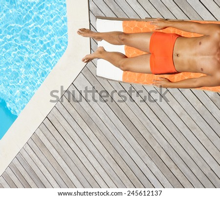 Side view of a young man lying by the swimming pool  - stock photo