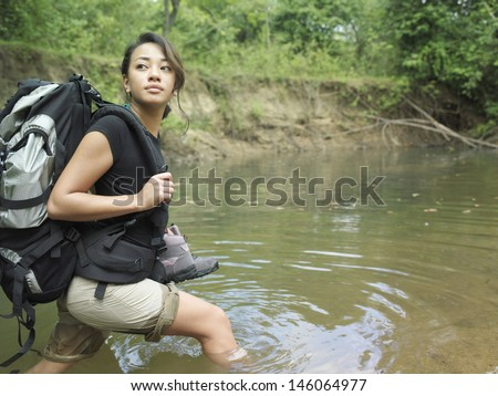 Side view of a young mixed race woman carrying backpack while walking in forest water - stock photo