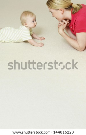 Side view of a young mother and child lying on floor - stock photo