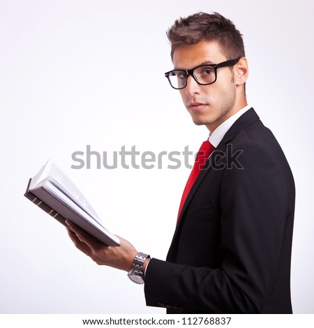 side view of a young student holding a book and looking at the camera - stock photo