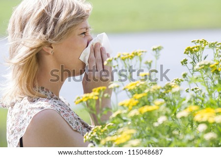 Side view of a young woman blowing nose into tissue in front of flowers - stock photo