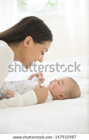 Side view of a young woman playing with her little baby in bed - stock photo