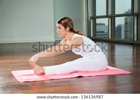 Side view of a young woman practicing yoga called Seated Forward Bend in gym - stock photo