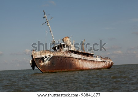 side view of abandoned wrecked ship in seaside landscape - stock photo
