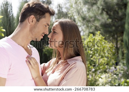 Side view of affectionate young couple looking at each other in park - stock photo