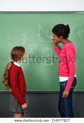 Side view of African American female teacher teaching mathematics to schoolgirl in classroom - stock photo