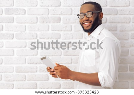 Side view of Afro American man in classic shirt and glasses using a tablet, looking at camera and smiling, standing against white brick wall - stock photo